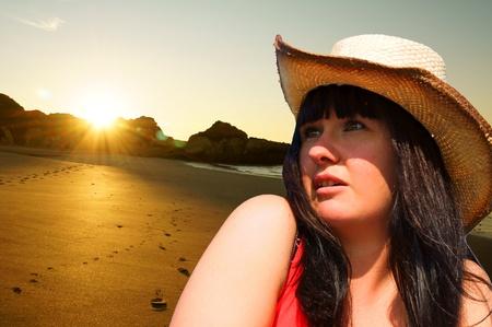 pretty girl on the beach watching the sunrise photo