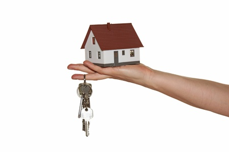 Hand holding a house with a bunch of keys