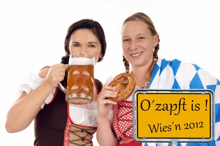 two pretty women in dirndl with pretzels and beer mug photo