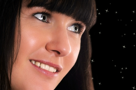 Portrait of a young brunette woman over a starry sky photo