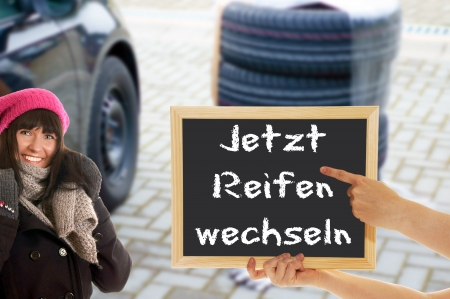 pneu: woman and a sign with the german words Now change tires Stock Photo
