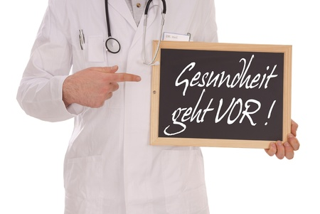 Doctor and sign with the german words Health comes first photo