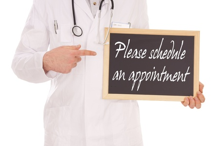 Doctor and sign with the words Please schedule an appointment photo