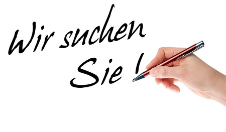 Hand with pen writes the german words We are looking for photo