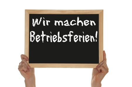 hands holding a sign with the german words We make holiday operation Stock Photo