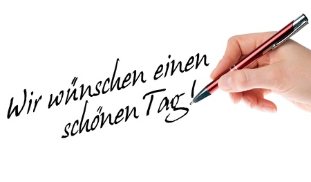 Hand with pen writes the german words Have a nice day Stock Photo - 16740880
