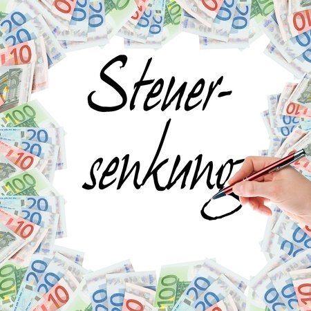 wage earner: Hand with pen writes the german words tax cut Stock Photo