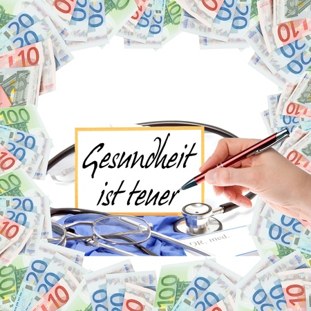 Frame bills and sign with the german words Health is expensive photo