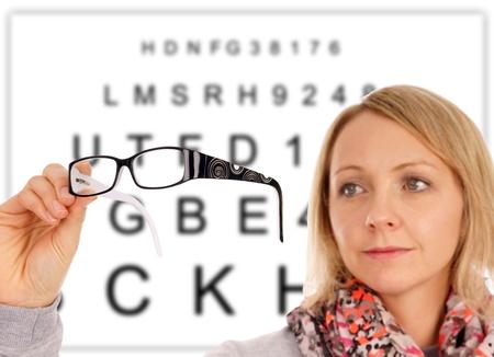 diopter: Mujer con gafas y el panel de examen de la vista