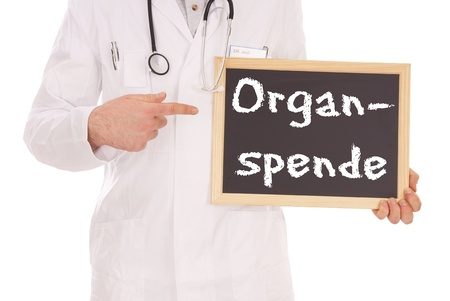 donacion de organos: Doctor y cartel con las palabras donaci�n de �rganos alem�n Foto de archivo