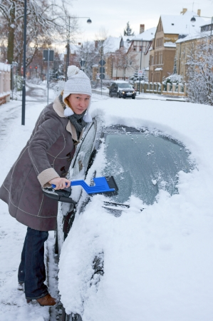 Woman remove snow from windshield photo
