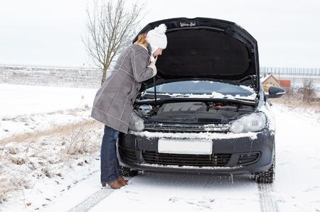 Autopanne - Frau schaut in den Motorraum