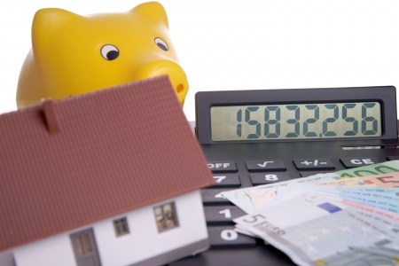 homeowners insurance: small house with calculator and euro money Stock Photo