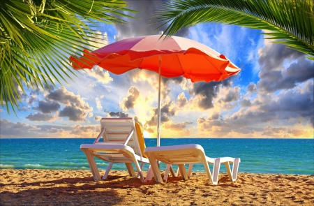 Beach chair and umbrella with palm trees on the beach Stock Photo