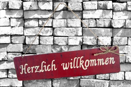 cordially: Sign on a stone wall and the german words cordially welcome Stock Photo