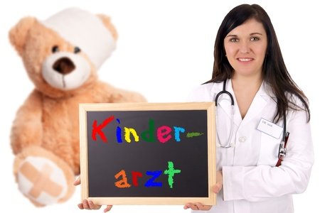 Doctor with teddy and shield with the german word Pediatrician photo