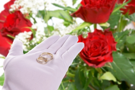 Hand holding Wedding Rings with roses background photo