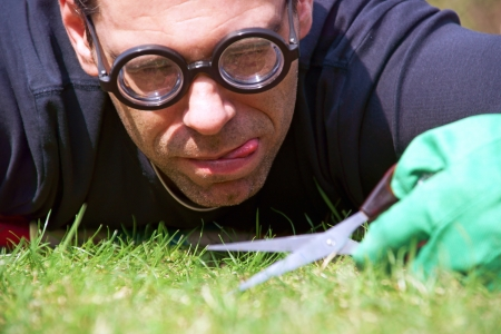 Man with scissors cultivates the lawn