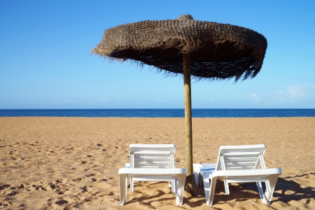 Beach with sunbeds and umbrella photo