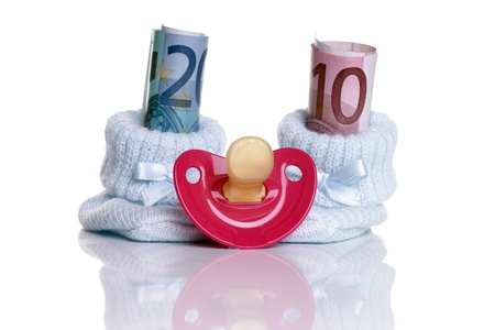 Baby shoes with baby teats and euro banknotes photo