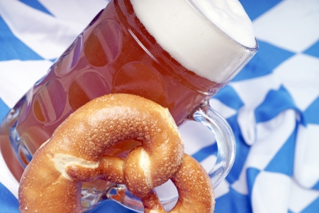 Beer mug with wheat beer and pretzel on a Bavarian flag photo
