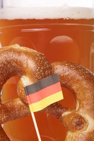 germany flag: Tazza di birra con birra bianca e pretzel con bandiera Germania