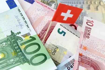 tratados: el dinero del euro con la bandera suiza Foto de archivo