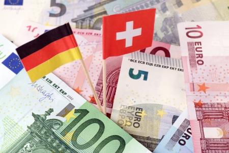 tratados: el dinero del euro con la bandera de Alemania y la bandera suiza
