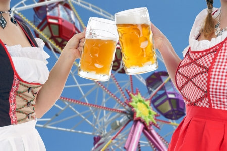 Two women in dirndls and beer mug in front of a ferris wheel photo