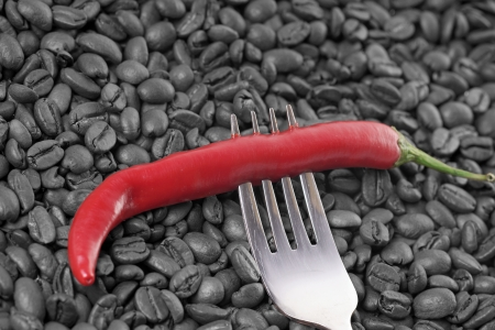 full bodied: Chili pepper on a fork with coffee beans Stock Photo