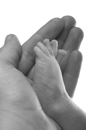 Hand holding a baby foot in black and white photo
