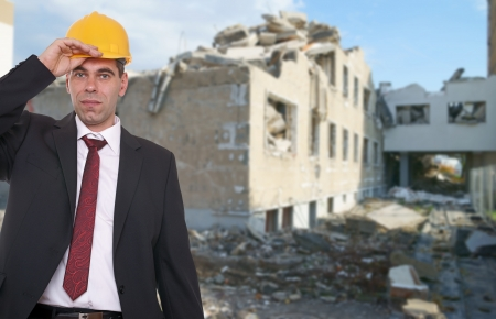 house demolition: Businessman with construction helmet in front of a house demolition