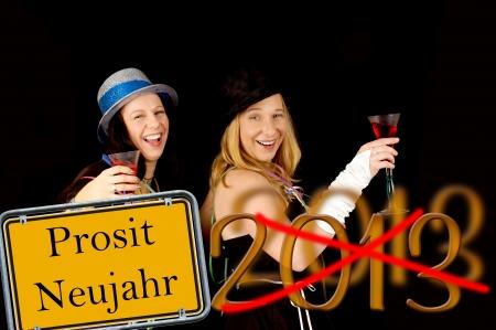 jahreswechsel: due donne che celebrano e scudo con le parole tedesche Prosit Neujahr