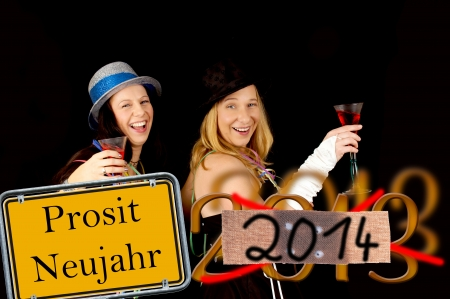 jahreswechsel: two women celebrating and shield with the german words Prosit Neujahr Stock Photo