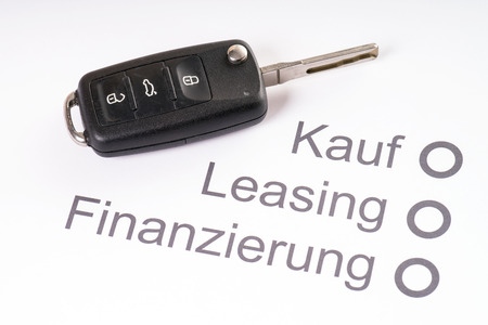 leasing: Car Key on a sheet of paper with the German words, buying, leasing and financing