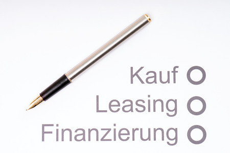 Pen on a sheet of paper with the German words, buying, leasing and financing photo