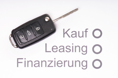 Car Key on a sheet of paper with the German words, buying, leasing and financing photo