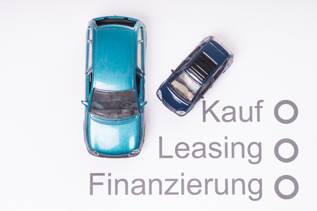 Model car on a sheet of paper with the German words, buying, leasing and financing photo