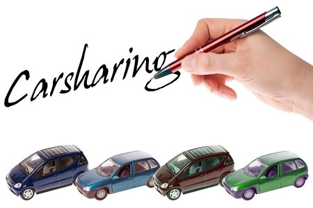 Hand with pen writes the word Carsharing photo