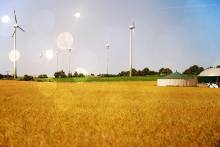Grain field with wind turbines and biogas system Standard-Bild