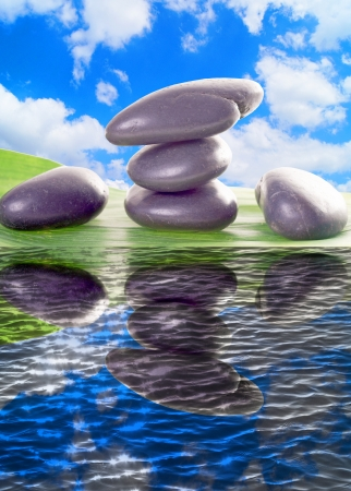 Hot Stones and blue sky over reflective water photo