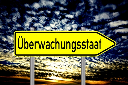 liberties: sign with the german words surveillance state over a dark sky