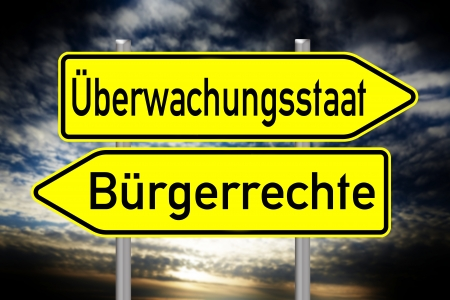 liberties: sign with the german words surveillance state and civil rights over a dark background Stock Photo