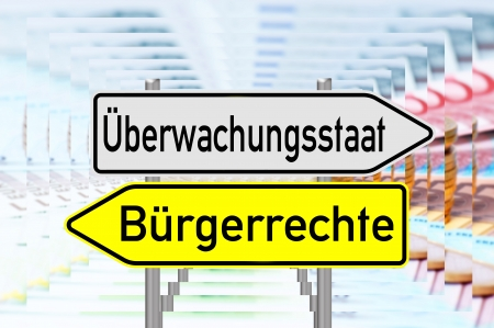 liberties: signpost with the german words surveillance state and civil rights over a reflective background with euro money