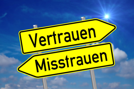 mistrust: Shield with the german words trust and mistrust over a blue sky with sun Stock Photo