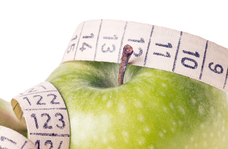 green apple with measuring tape over a white background photo