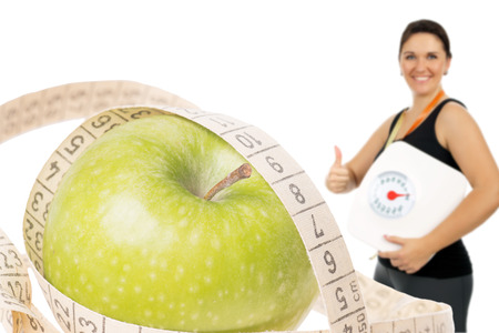 Apple with measuring tape and woman with the body scale photo