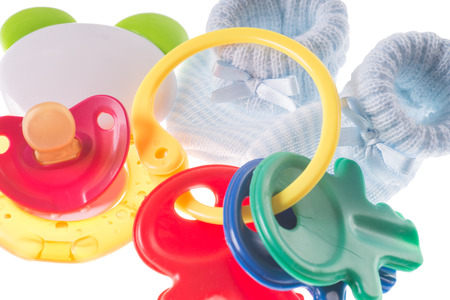teether: Baby toy with teether and baby shoes Stock Photo