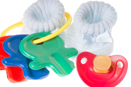 teats: Baby toy with pacifier and baby shoes Stock Photo