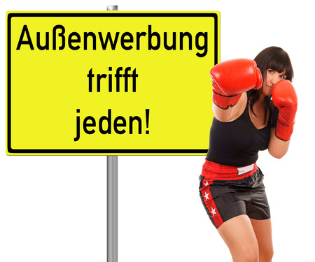 woman with boxing gloves and advertising sign with the german words outdoor advertising strikes everyone photo
